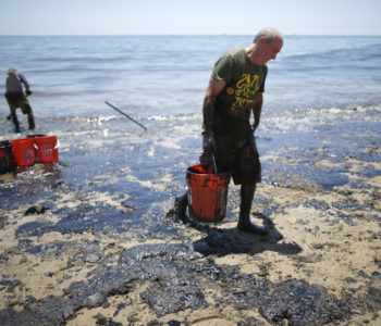 William McConnaughey, 56, (R) who drove from San Diego to volunteer, carries buckets of oil from an oil slick in bare feet along the coast of Refugio State Beach in Goleta, California, United States, May 20, 2015. A pipeline ruptured along the scenic California coastline on Tuesday, spilling some 21,000 gallons (79,000 liters) of oil into the ocean and on beaches before it could be secured, a U.S. Coast Guard spokeswoman said. REUTERS/Lucy Nicholson